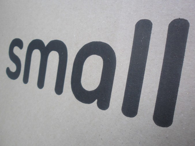 the word small in lower case, each letter increasing in size, achieved with the angle of the camera shot from printed material ie. the side of a box